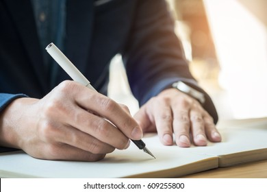 Businessman writing in a document. Focus on the tip of the pen.