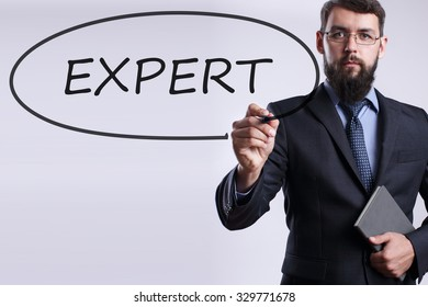 Businessman writing Expert with marker on transparent board. Business, internet, technology concept.