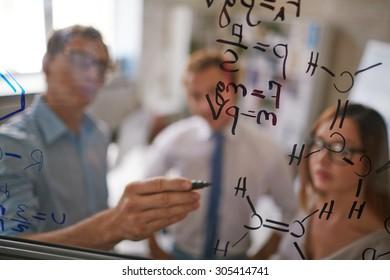 Businessman writing formulae on transparent board
