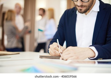 Businessman writing in his notepad in office