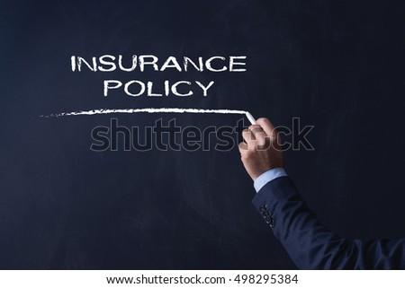 businessman writing insurance policy on blackboard