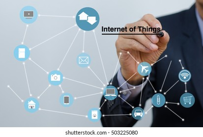 Businessman writing internet of things on virtual screen and things web icons, modern trading, internet of things concept, smart business.