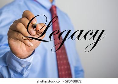 Businessman writing Legacy word on virtual screen.