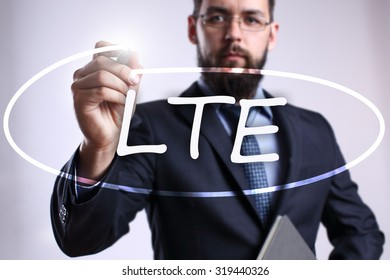 """Businessman writing """"LTE"""" with marker on transparent board. Business, internet, technology concept."""