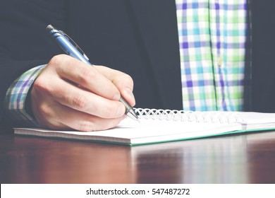 Businessman is writing a memo with a pen. Business outfit. Image has a vintage effect applied.