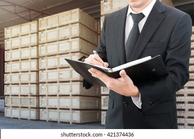 Businessman writing notebook with blurred cargo in wooden case at warehouse background