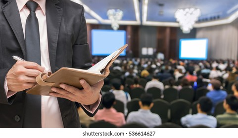 Businessman writing the notebook on the Abstract blurred photo of conference hall or seminar room with attendee background