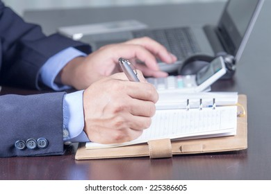 businessman writing in notebook on the desk in office