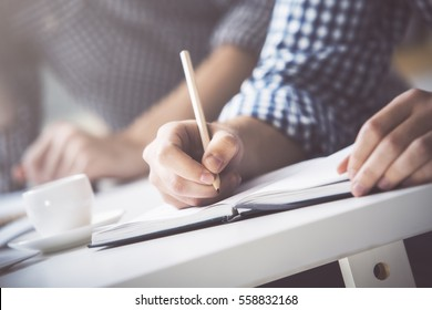 Businessman writing in notepad placed on desktop with coffee cup, supplies, equipment and other items. Close up