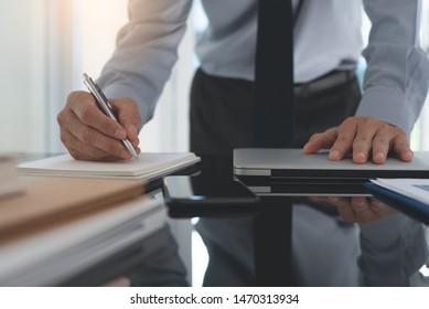 Geschäftsmann, der Notizen auf Papier schreibt, während er an Laptop-Computern im modernen Büro arbeitet. Projektleiter plant seine Arbeit auf Notebook mit Mobiltelefon am Büroschreibtisch, Nahaufnahme