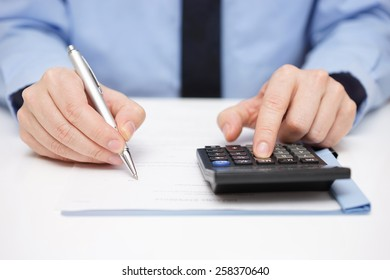 Businessman writing on document and using calculator at the same time