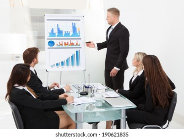 Businessman writing on flipchart while giving presentation to colleagues in office