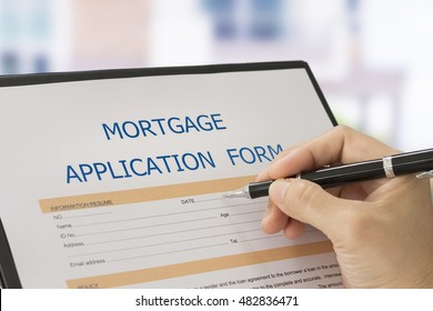 Businessman writing on the mortgage loan application form with house background. Mortgage Concepts.