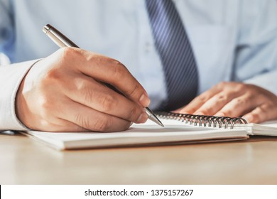 businessman writing on note book in office