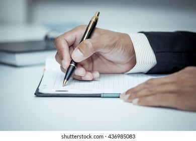 Businessman writing on notebook with pen in the office in blue color tone