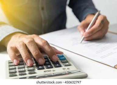 Businessman writing on notebook using calculator