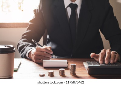 businessman Writing paper and using calculator Calculating bonus(Or other compensation) to employees to increase productivity. on desk.Selective Focus