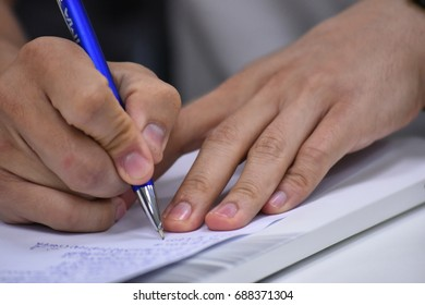 Businessman writing with pen in notepad