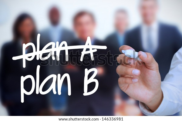 Businessman writing plan B with a marker in front of a business team