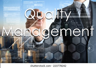 the businessman is writing Quality Management on the transparent board with some diagrams and infocharts with the city in the background