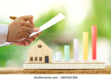 Businessman writing or signing on the business document and home model and bar graph with blur background in the public park, Buy or sell a house and real estate for working capital concept.