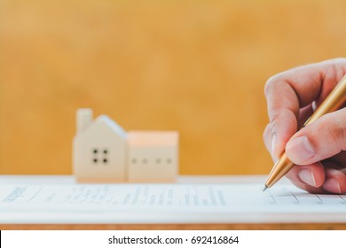 Businessman writing or signing on document business agreement contract with golden pen on home for family background for buy or mortgage as loan for new real estate and house concept.