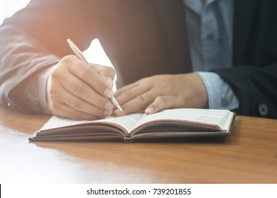 A businessman writing something in his note pad while sitting at the desk table  in his office. Business concept.