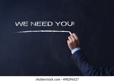 Businessman writing WE NEED YOU! on Blackboard