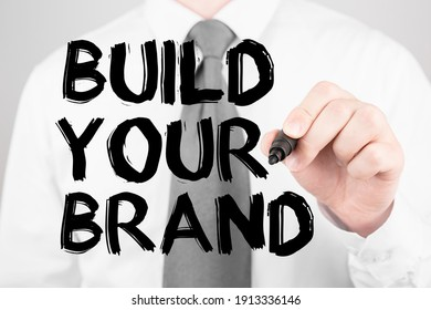 Businessman writing word Build your brand with marker, Business concept
