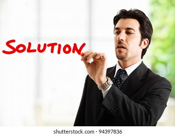"""Businessman writing the word """"solution"""""""
