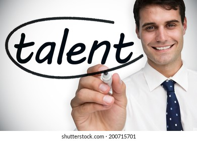 Businessman writing the word talent against white background with vignette