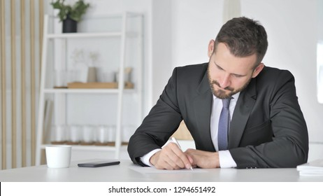 Businessman Writting Documents in Office