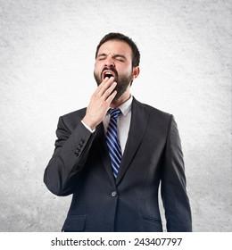 Businessman yawning over textured background