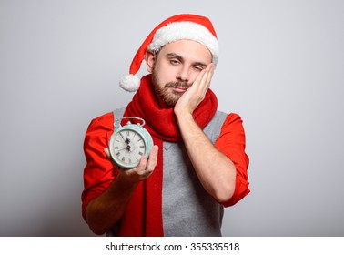 Businessman yawning stretching after sleeping with an alarm clock. Happy man wearing Santa hat on New Year's corporate parties. Studio photo, isolated