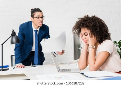Businessman yelling at businesswoman by table in office
