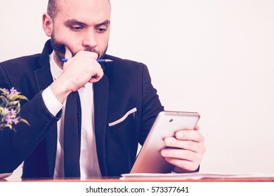 Businessman young and attractive working on a tablet PC in the office