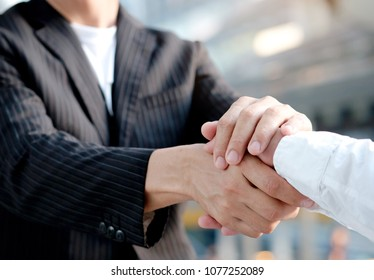 Businessman and young man holding hands to take care and help each other.Business and investment Concept