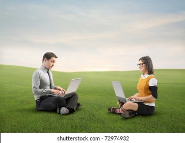 Businessman and young woman using laptops on a green meadow