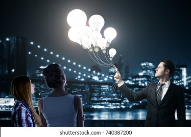 Businessman and young women holding abstract glowing lamp balloons on blurry night city background. Imagination concept