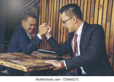 Businessmann armwrestling, exerting pressure on each other, looking eyes in eyes, struggling for leadership.Business rival comptetition concept