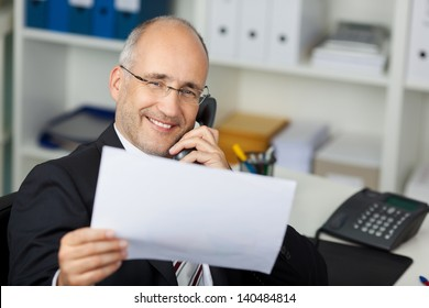 businessmann reading document while calling on the phone