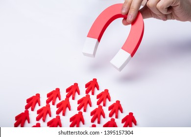Businessman's Hand Attracting Red Team With Horseshoe Magnet On White Background