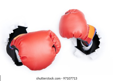 Businessman's hand breaking through a paper wall wearing boxing gloves