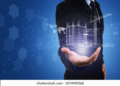 Businessman's hand with building construction design reality virtual technology. Building automation digital wireless control concept.