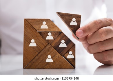 Businessman's hand building tangram square block with human figures