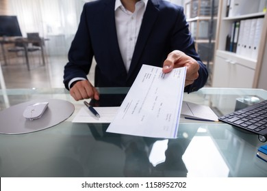 Businessman's Hand Giving Cheque Over Glass Desk