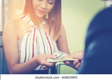 Businessman's hand is giving money for Business woman.