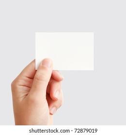 Mano del empresario con tarjeta de presentación de papel blanco en blanco, cerrado aislado en fondo gris cuadrado