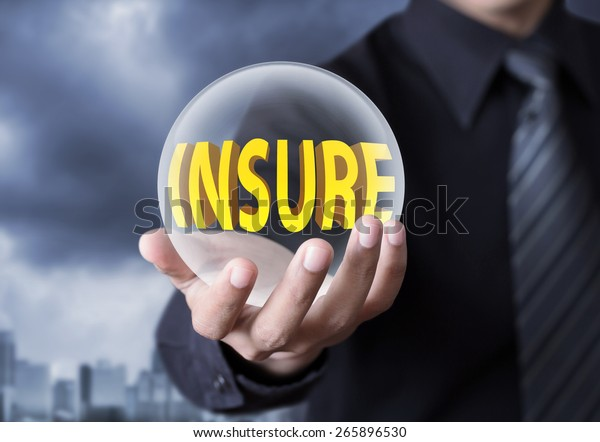 Businessman's hand holding crystal ball of insurance concept