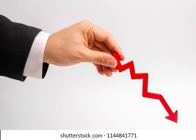 A businessman's hand is holding a red arrow down on a white background. The concept of reducing costs and profits, falling living standards and prices. Decreased projections, depressed economies.